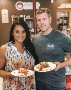 Couple holding finished meals from scratch